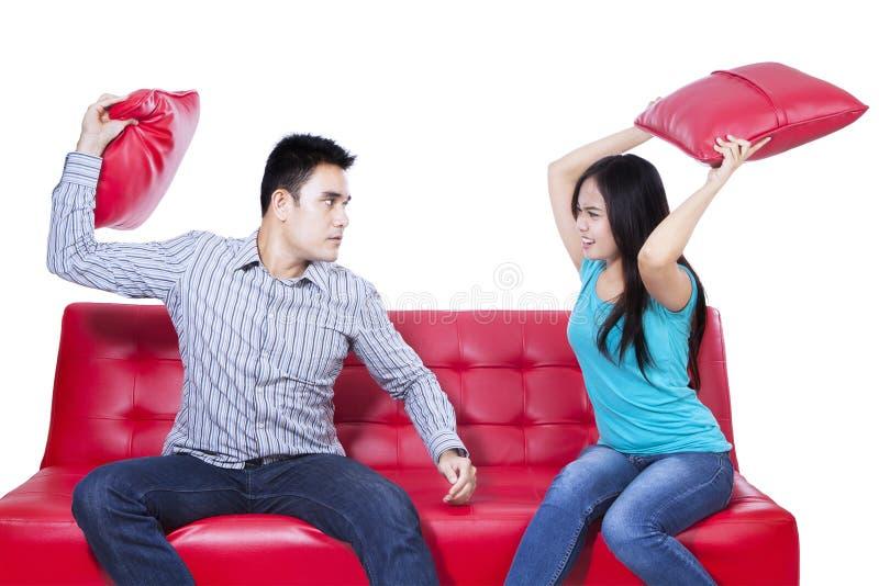 Combat de couples sur le sofa rouge - d'isolement photographie stock