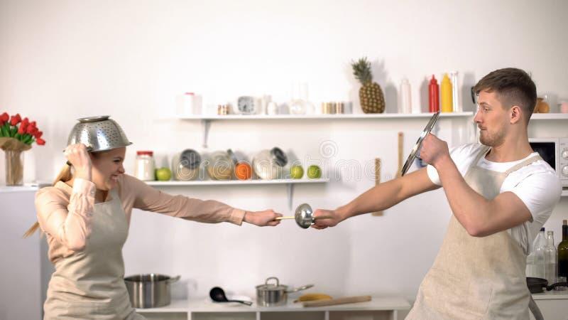 Combat drôle de couples avec la vaisselle de cuisine, feignant pour être chevaliers, ayant l'amusement photographie stock libre de droits