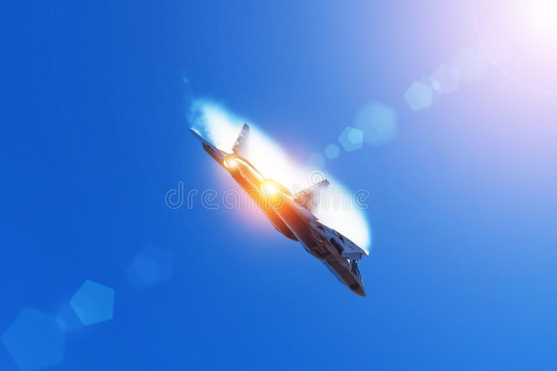 Combat fighter flies performing a maneuver in the air with clouds behind the wings, low pressure area. Sun glare from the bright. Sun and light from the nozzle stock image