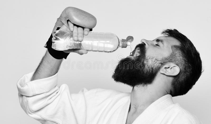 Combat master drinks refreshing water after training. Karate man with satisfied face in boxing gloves holds water bottle. Japanese martial arts concept. Man stock photos