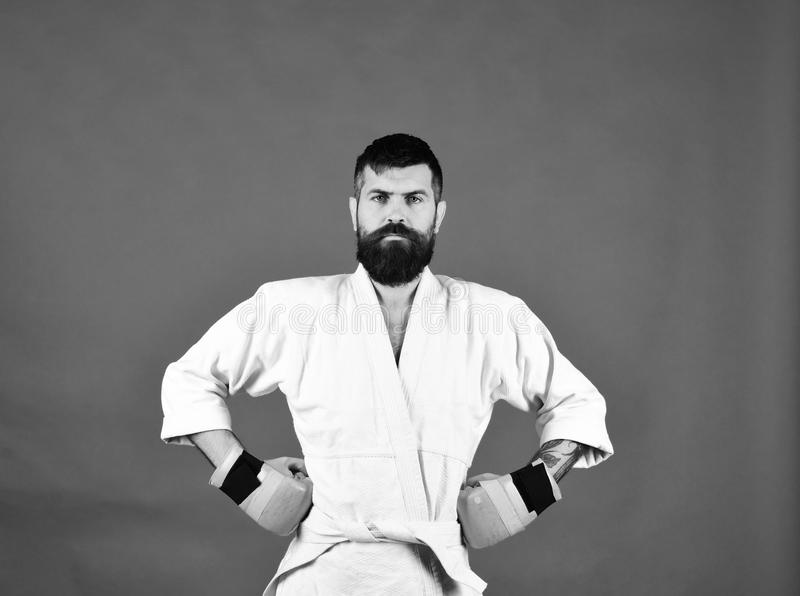 Combat master poses demonstrating muscles. Japanese martial arts concept. Karate man with serious face in uniform and golden boxing gloves. Man with beard in stock photography