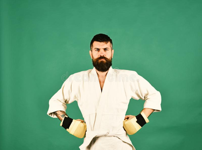 Combat master poses demonstrating muscles. Japanese martial arts concept. Karate man with serious face in uniform and golden boxing gloves. Man with beard in stock photo