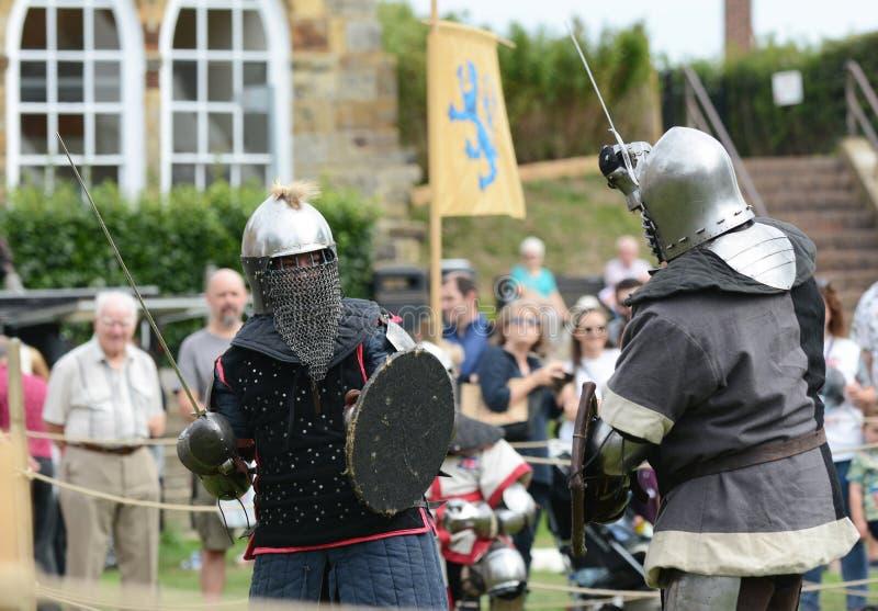 Combata en duelo entre los combatientes en vestido medieval del este y al oeste foto de archivo