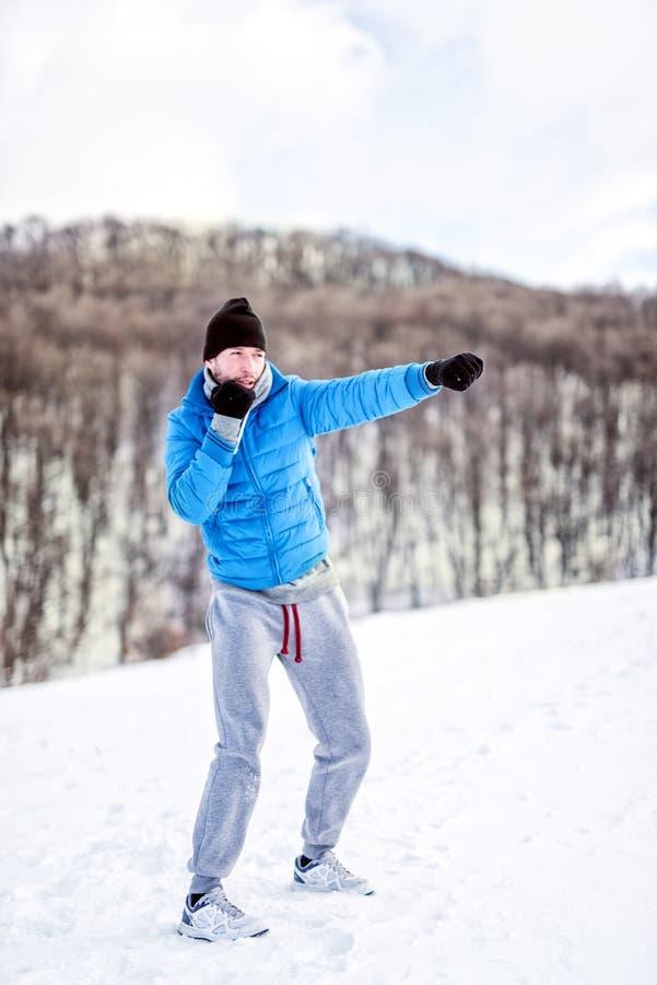 Combatiente del atleta que hace un entrenamiento de la práctica en la nieve, ejercitando foto de archivo libre de regalías