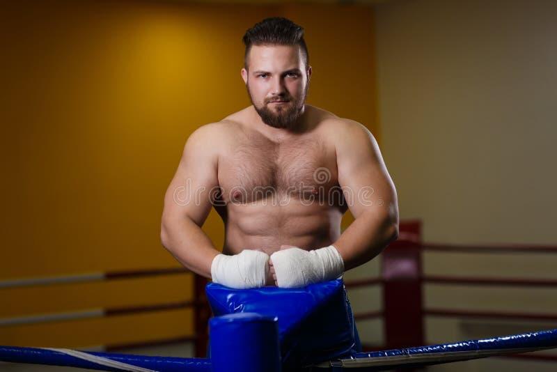 Combatiente del hombre fuerte que se coloca en el ring de boxeo foto de archivo