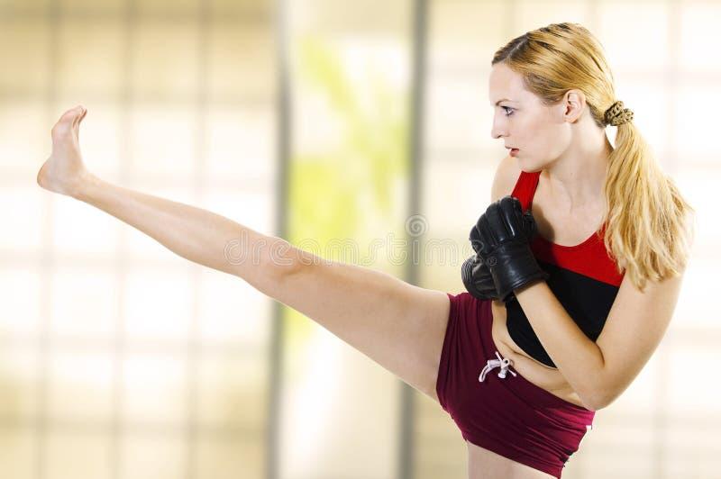Combatiente femenino que golpea la alta cara de la pierna con el pie. Aptitud fotografía de archivo