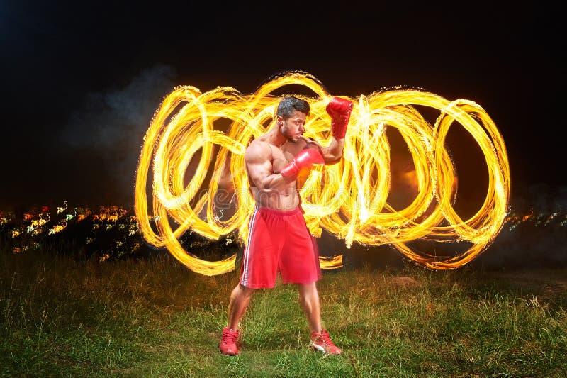Combatiente masculino muscular fuerte con el fuego y las llamas detrás de su CCB fotografía de archivo libre de regalías