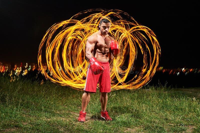 Combatiente masculino muscular fuerte con el fuego y las llamas detrás de su CCB foto de archivo libre de regalías