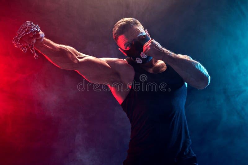 Combatiente muscular serio que hace el sacador con las cadenas trenzadas sobre su puño imágenes de archivo libres de regalías