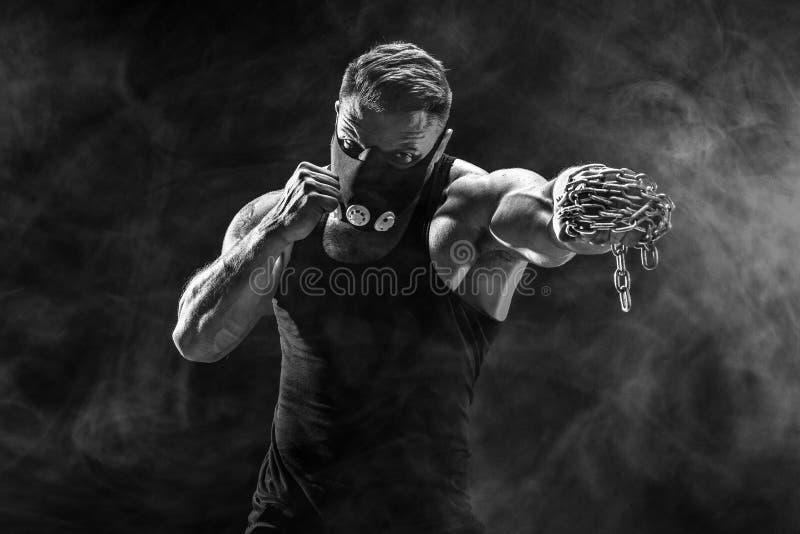 Combatiente muscular serio que hace el sacador con las cadenas trenzadas sobre su puño imagenes de archivo