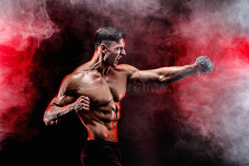 Combatiente muscular serio que hace el sacador con las cadenas trenzadas sobre su puño imagen de archivo