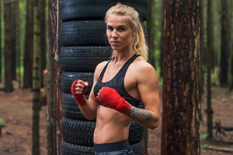 Combatiente profesional del boxeador de la mujer que presenta en la postura del boxeo, resolviéndose al aire libre fotos de archivo