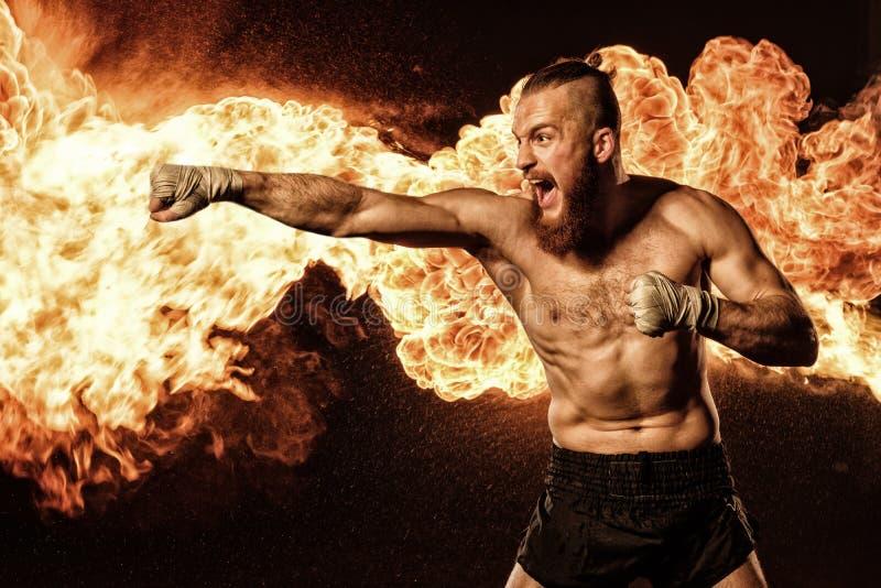 Combatiente profesional shadowboxing con el fuego y las chispas en fondo foto de archivo