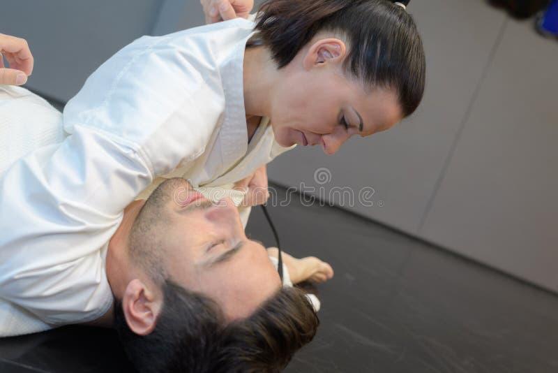 Combatientes del judo de la mujer joven y del hombre en pasillo de deporte foto de archivo libre de regalías