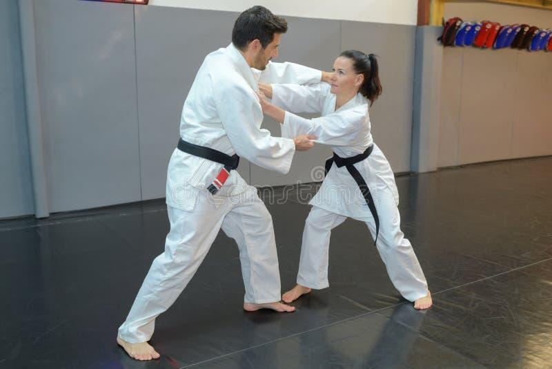 Combatientes del judo de la mujer y del hombre en pasillo de deporte imagen de archivo