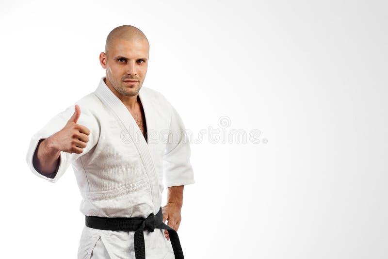 Combattant dans le kimono blanc posant sur d'isolement image libre de droits