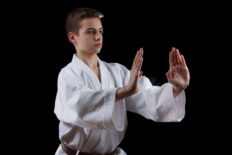Combattant de karaté dans le kimono blanc d'isolement sur le noir photographie stock libre de droits