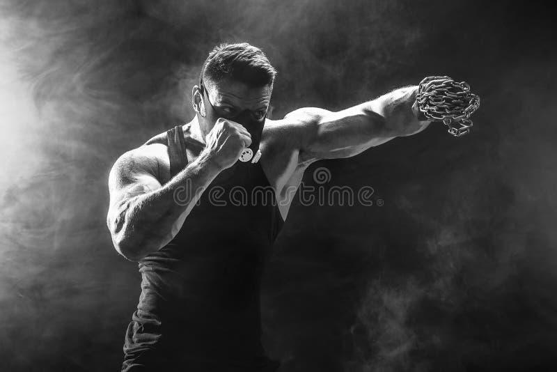 Combattant musculaire sérieux faisant le poinçon avec les chaînes tressées au-dessus de son poing images libres de droits