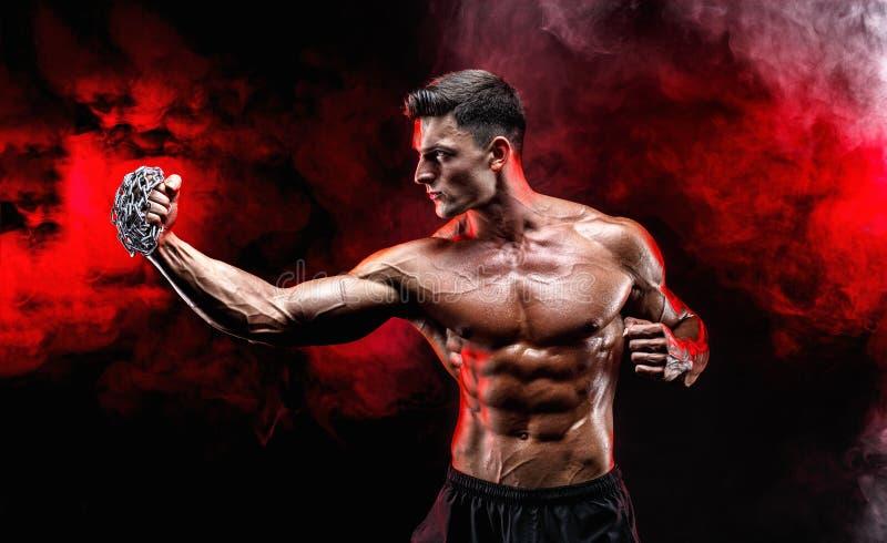 Combattant musculaire sérieux faisant le poinçon avec les chaînes tressées au-dessus de son poing photo libre de droits