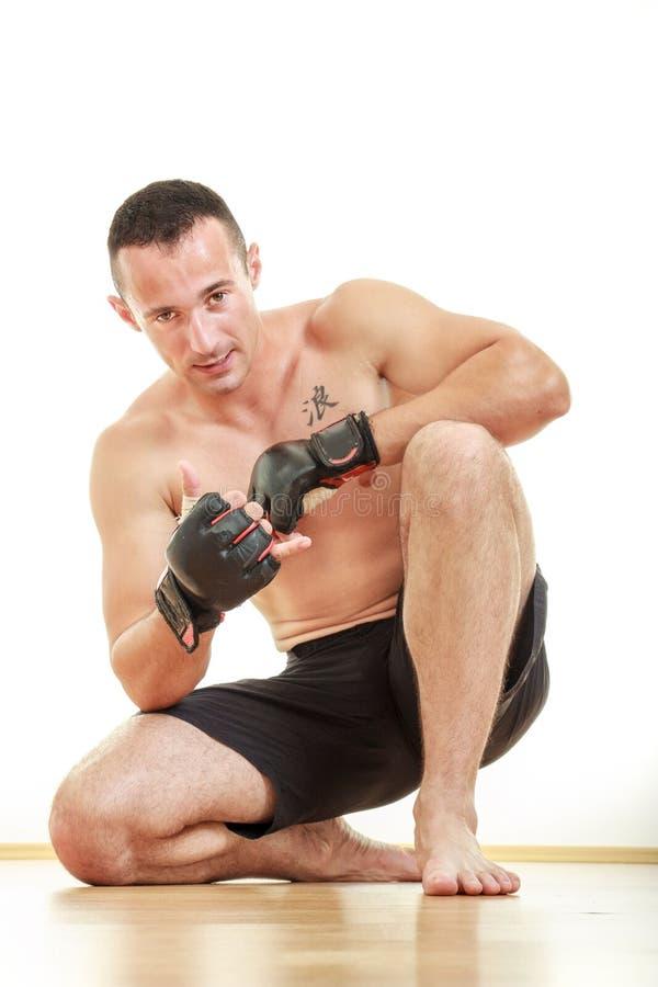 Combattant sans chemise beau de jeune homme avec des gants de sport photographie stock