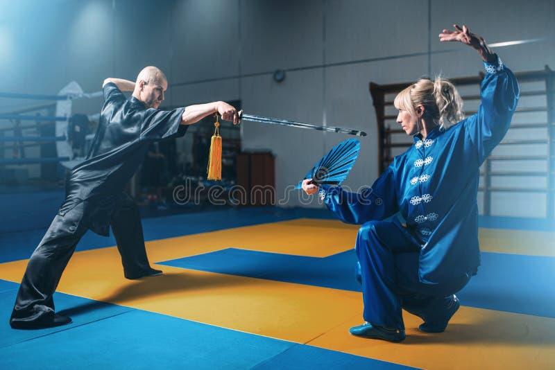 Combattants de Wushu, homme avec l'épée et femme avec la fan images libres de droits