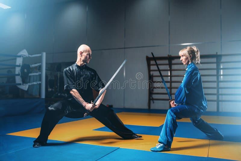 Combattants, homme et femme de Wushu avec des épées images stock