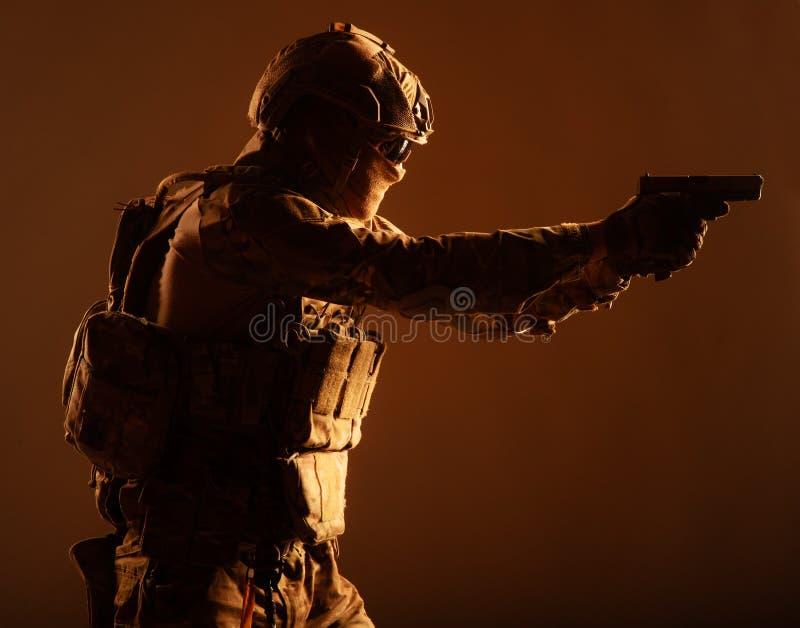 Combattente antiterroristico della squadra che tende con la pistola fotografia stock