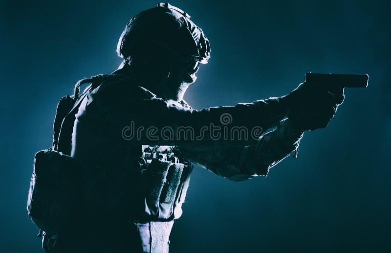 Combattente antiterroristico della squadra che tende con la pistola immagine stock