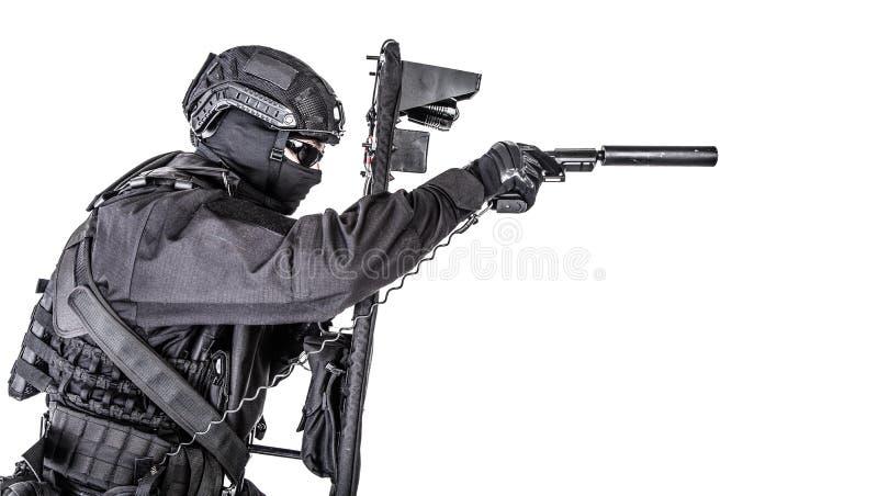 Combattente dello SCHIAFFO che si nasconde dietro lo schermo balistico su bianco immagine stock libera da diritti