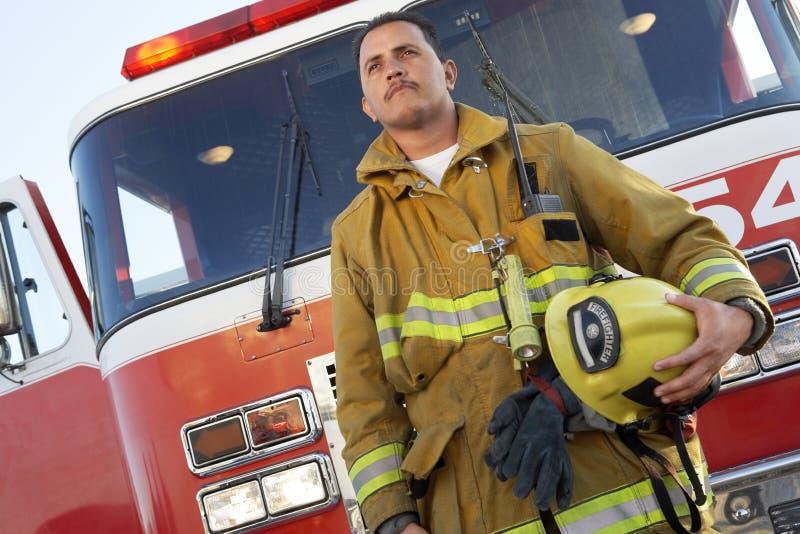 Combattente di fuoco che sta in Front Of Fire Engine fotografie stock