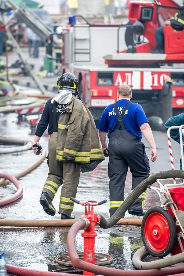 Combattente di fuoco e soccorritore che si allontanano costruzione nelle gocce di acqua dopo avere messo fuori immagine stock