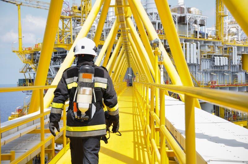 Combattente di fuoco su olio e su industria del gas, riuscito pompiere sul lavoro fotografie stock