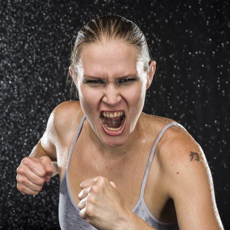 Combattente femminile irato che grida alla macchina fotografica fotografia stock