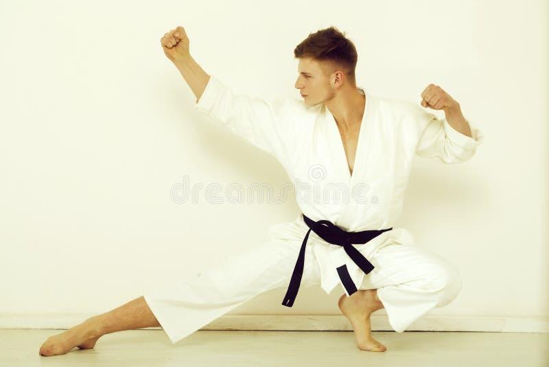 Combattente, forte karatè che posa nella posizione combattente bassa fotografia stock