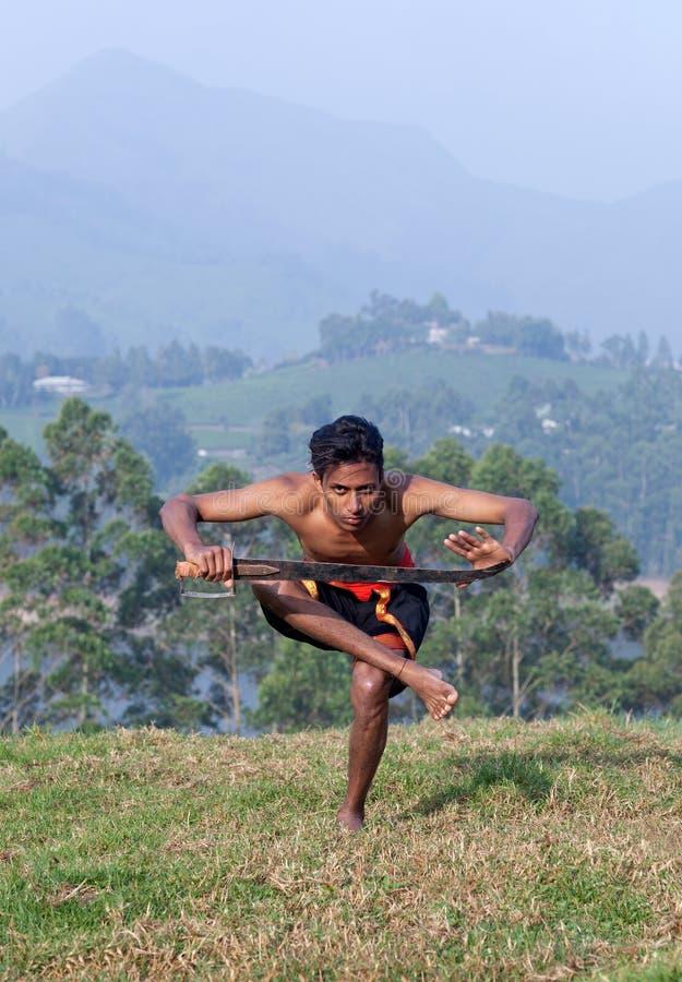 Combattente indiano che fa gli esercizi con la spada durante il Kalaripayattu m. fotografie stock