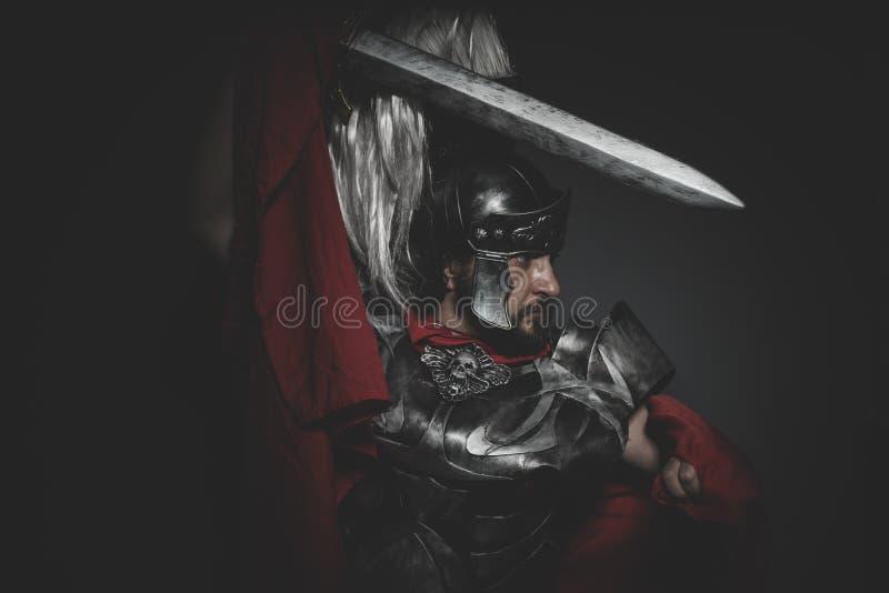 Combattente, legionario romano pretorio e mantello, armatura e swo rossi fotografie stock libere da diritti