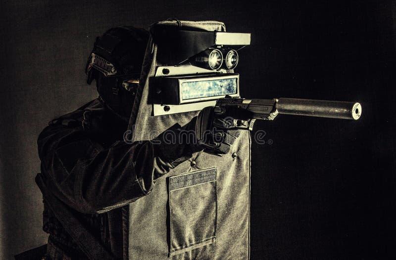 Combattente munito dello SCHIAFFO che si nasconde dietro lo schermo balistico immagine stock