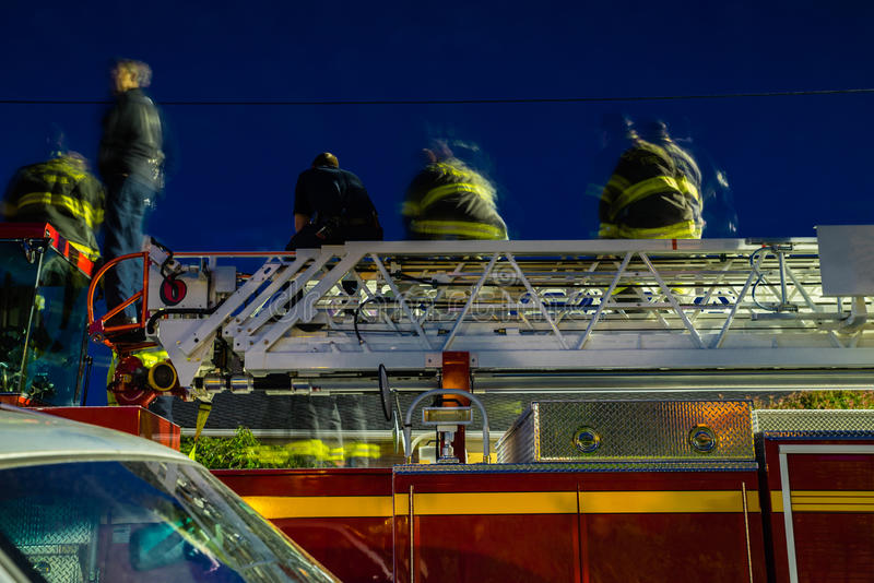 Combattenti di fuoco sul camion dei vigili del fuoco alla notte fotografia stock libera da diritti