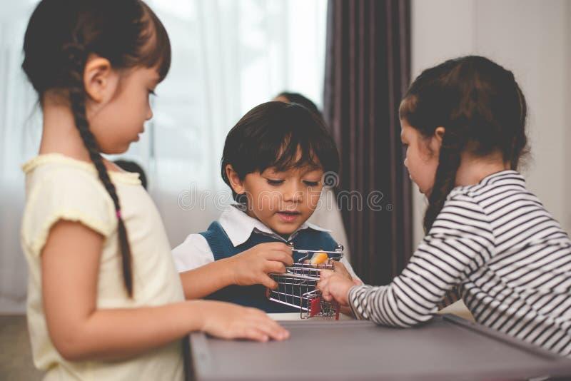 Combattimento caucasico del ragazzo per i giocattoli con le sue sorelle Famiglia e concetto dei bambini Tema di litigio e di conf immagine stock libera da diritti