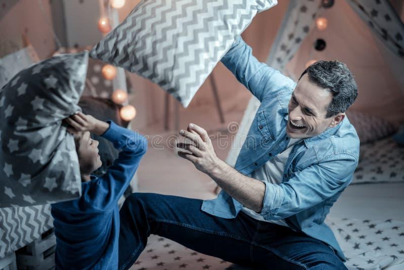 Combattimento contentissimo del giovane con i cuscini immagini stock libere da diritti