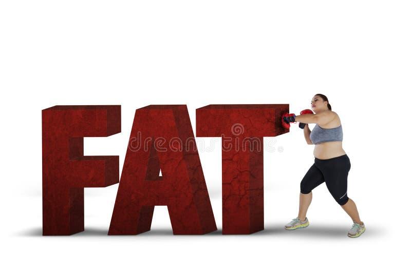 Combattimento grasso della donna con la parola grassa fotografie stock