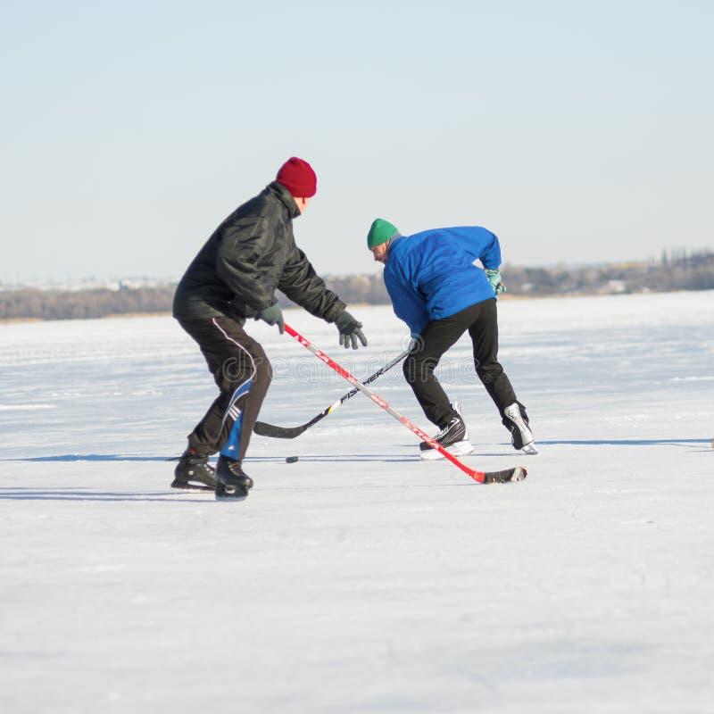Combattimento maturo dell'uomo due per il pacchetto mentre giocando hockey su un fiume congelato Dnepr in Ucraina fotografia stock