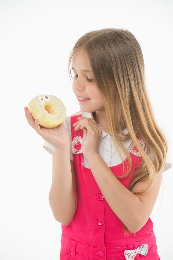 Combien mauvais sont les bonbons pour vos enfants Le visage de sourire mignon de fille tient le beignet doux La fille aime des bo photos libres de droits