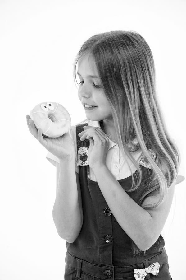 Combien mauvais sont les bonbons pour vos enfants Le visage de sourire mignon de fille tient le beignet doux La fille aime des bo photo libre de droits