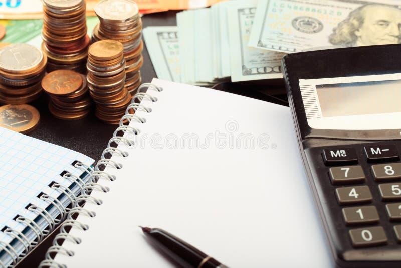 Combinación financiera del concepto del negocio con las monedas, el dinero, la calculadora y la pluma imagen de archivo