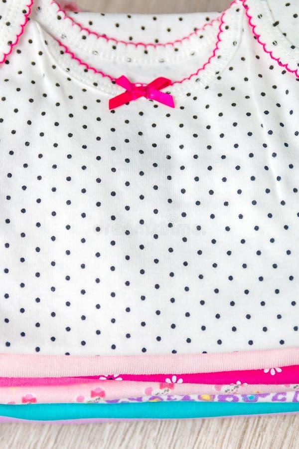 Combinaison rose et blanche pliée là-dessus fond en bois gris couche-culotte pour la fille nouveau-née Pile d'habillement infanti photos libres de droits