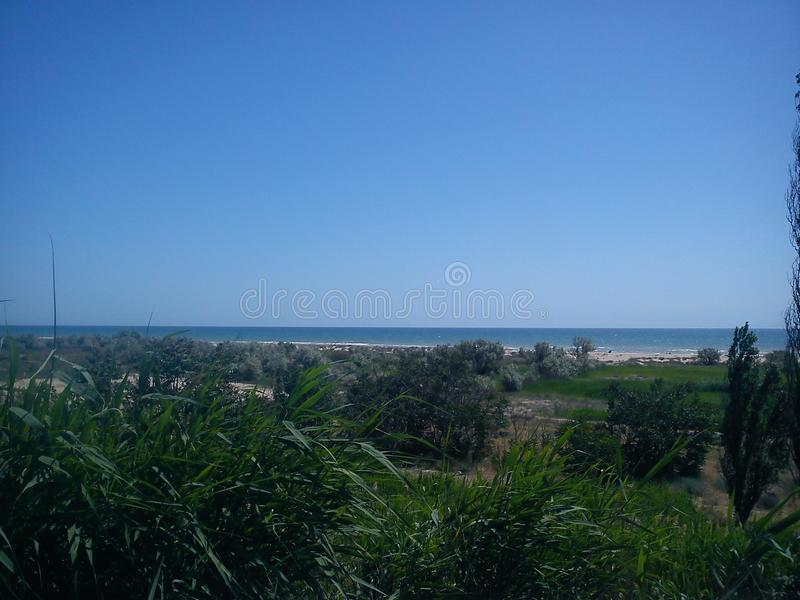 The combination of calm deep sea, deep blue sky and life on the shore calms. royalty free stock photos