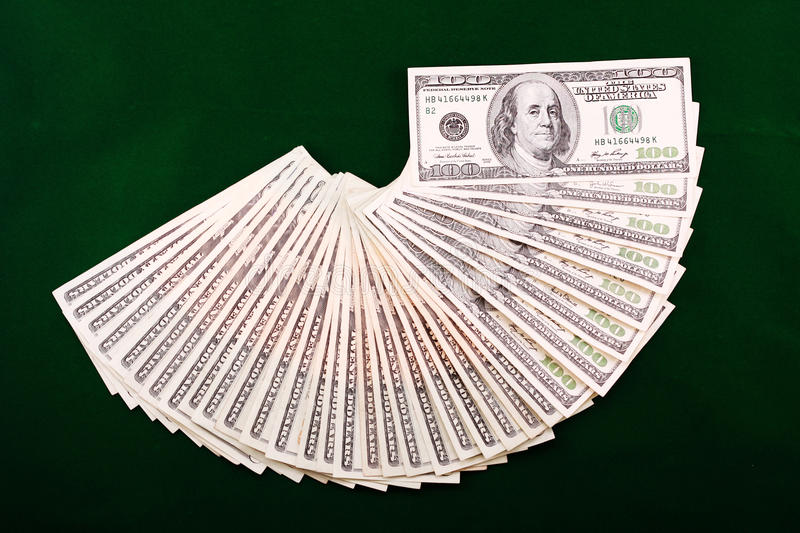A Combination Of Dollar Fan Over A Green Backgroun Royalty Free Stock Image