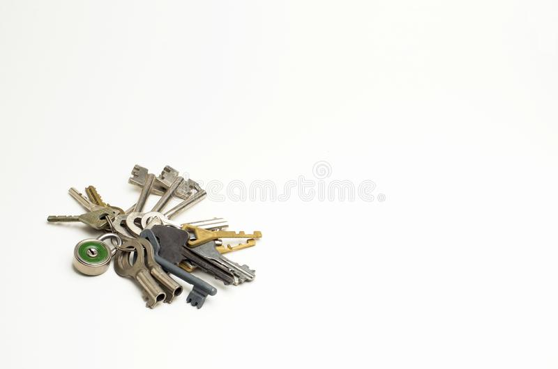 The combination of fifteen different keys and a padlock lying on the plane, copy space. royalty free stock photography