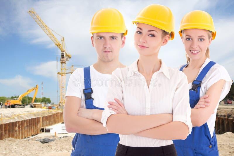 Combine el concepto del trabajo - dos mujeres jovenes y hombre en el constructor azul 's u foto de archivo libre de regalías